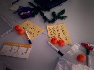 """Auf dem Tisch liegen Mandarinen, Eddings, Sticky Notes, ein Tesa und zwei Zettel, auf denen steht: """"Wie fühle ich mich gerade?"""" und """"Wie habe ich mich hauptsächlich gefühlt?"""""""